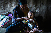 21 year old, Rekha RAMESH feeds the nutritionist meal of eggs to her 18 month old Prahlad RAMESH, a recovering malnourished boy in their house in Dhawati VIllage of Khaknar block of Burhanpur district in Madhya Pradesh, India.  Photo: Sanjit Das/Panos for ACF