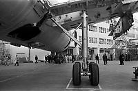 Usine de l'Aérospatiale de Saint-Martin-du-Touch, grand hall de montage. 5 février 1972. Vue d'ensemble du train d'atterrissage droit de l'avion Airbus A300 B ; vue en contre-plongée d'une partie du dessous de l'avion ; en arrière-plan techniciens, échaffaudages. Cliché pris lors du 1er déplacement tracté de l'avion encore en cours de montage.
