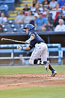Asheville Tourists shortstop Jose Gomez (4) swings at a pitch during a game against the Greenville Drive at McCormick Field on April 15, 2017 in Asheville, North Carolina. The Tourists defeated the Drive 5-4. (Tony Farlow/Four Seam Images)