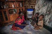 Uganda, Mpigi. Allan Makayenga has no electricty in her home so she uses the solar light products. Allan uses Purifaaya water filtration products as she serves water to her grandchildren, Imacurate Among and Umour Walugembe