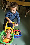 Education Preschool Child care all day program for two year olds boy pushing toy doll carriage with doll and other toys inside