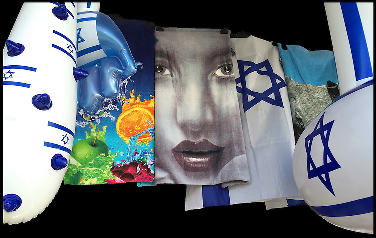 """2. """"Jaffa is more than Oranges"""":  beach towels and inflatable toys in a shopfront display, Tel Aviv.<br /> <br /> When I first made this image in Tel Aviv, what struck me hard was the Semitic face emblazoned on a bath towel. Flanked by the Israeli flag and Jewish stars of David, this storefront seemed to trumpet pride in a quintessentially Jewish nation-state; yet the exaggerated classic Semitic face could represent an Arab or Jew.<br />  <br /> Tel Aviv was founded in 1909 on the outskirts of the ancient port of Jaffa by Jewish immigrants, many of whom bought orange groves from Jaffa's Arab residents and developed a thriving agricultural trade. But in 1921, this """"harmonious co-existence"""" erupted into riots between Arabs and Jews, who then moved en masse to Tel Aviv. Today, Tel Aviv is the 2nd largest city in Israel (after Jerusalem) and, according to the Global Financial Centres Index, is the 25th most important financial center in the world. So now I wonder, what do these towels signify?"""