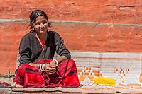 Nepal, Kathmandu.  Young Woman Sitting, with Nose Pin and Bindi.  Kumkuma Powder just below her hair part indicates she is married.