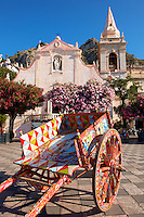 Traditional Sicilian cart infront of the Church of St. Guiseppe on the Plaza ix Aprile with trees in blossom - Taormina, Sicily