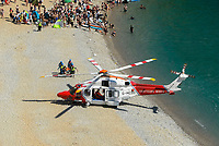 BNPS.co.uk (01202 558833)<br /> Pic: Graham Hunt/BNPS<br /> <br /> The coastguard helicopter lands on the beach at Durdle Door in Dorset to deal with a medical emergency on an afternoon of scorching hot sunshine and clear blue skies.<br /> <br /> The casualty is stretched to the coastguard helicopter.