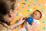 Occupational therapist working with infant to help her use two hands to hold ball, baby has Down syndrome