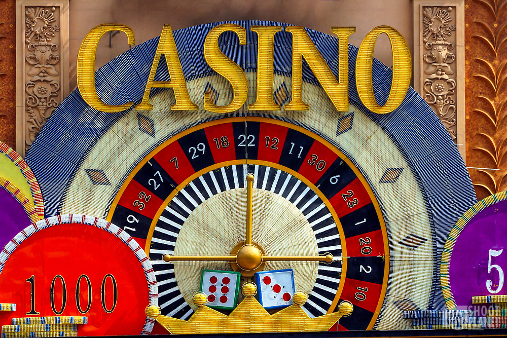 Close-up on an old casino sign, depicting a roulette game and casino coins, in the vibrant city of Macao, China