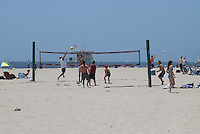Beach Volleyball, Santa Monica Beach. Santa Monica,CA.  Beachscape with a group of friends -- men and women -- playing volleyball on the beach.  One of the players is jumping to spike the ball on the opponents.  Typical weekend beach scene with sun, sand, sea, and sailboat.  Other people are sunning themselves.