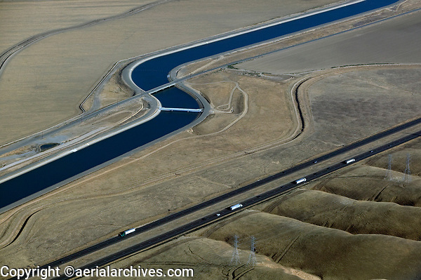 aerial photograph of the California Aqueduct, Central Valley, California running parallel to interestate I-5 and electric power transmission lines
