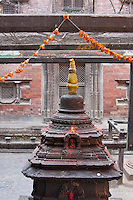Kathmandu, Nepal.  A Chaitya, or Stupa, Symbol of Religious Harmony, in the Courtyard of the Kumari Behal, house of the Kumari Devi, a Young Girl Revered as a Goddess by the Hindus of Kathmandu.  This particular stupa is dedicated to Saraswati, the goddess of learning.