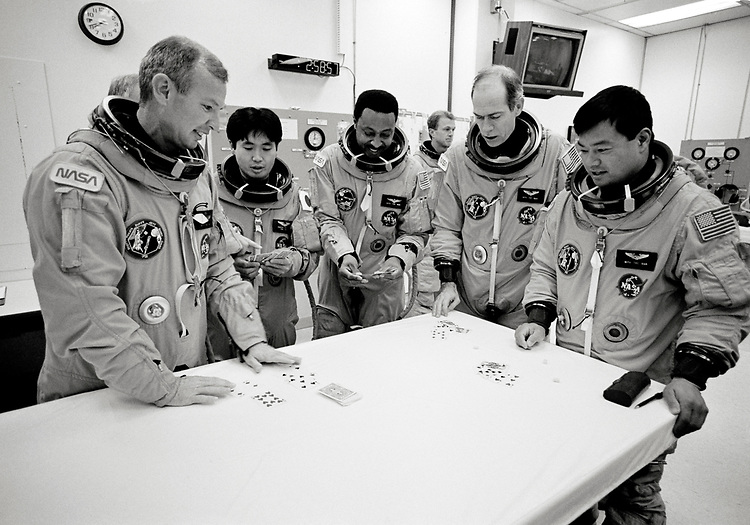 Image copyright John Angerson. <br /> STS-72 mission training.<br /> The crew play cards before the STS-72 simulated launch. Commander Brian Duffy, Pilot Brent W. Jett, Mission Specialists Leroy Chiao, Daniel T. Barry, Winston E. Scott, and Koichi Wakata.<br /> Kennedy Space Center, Florida, USA.