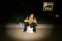CHINA. Beijing. A woman, eating KFC in the street. 2008.