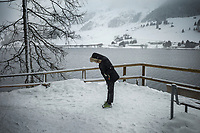 Switzerland. Canton Graubünden. Davos. Winter season. A woman looks at her feet during a snow storm. Lake Davos (German: Davosersee) is a small natural lake. Its surface area is 0.59 km² and the maximum depth is 54 m. Fed by sources of the Rhine, Flüelabach and Totalpbach, among other mountain creeks, the lake is used as a hydropower reservoir. Davos is an Alpine town, and a municipality in the Prättigau/Davos Region in the canton of Graubünden. 25.10.2020 © 2020 Didier Ruef
