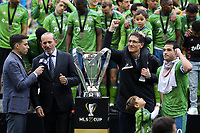 SEATTLE, WA - NOVEMBER 10: ESPN announcer Sebastian Salazar holds a microphone for MLS Commissioner Don Garger while Seattle Sounders FC owner Adrian Hanauer and team captain Nicolas Lodeiro #10 celebrate while waiting to be presented the Philip F. Anschutz Trophy during a game between Toronto FC and Seattle Sounders FC at CenturyLink Field on November 10, 2019 in Seattle, Washington.