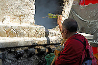 Tibetan Buddhist pilgrim throwing juniper twigs into an incense burner on the Barkhor pilgrim circuit around the Jokhang Temple, Lhasa, Tibet.