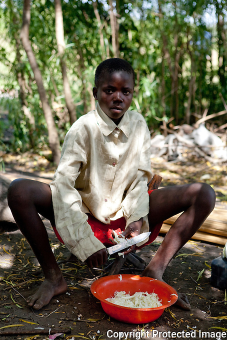 walter, an Aids Orphan prepares a meal for himslef and his  younger brother in Homa Bay, kenya.