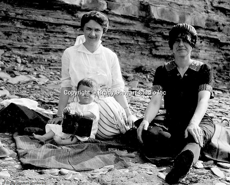 Erie PA:  Sarah and Helen Stewart relaxing on the Lake Erie shore with Sarah's sister.  Helen is holding one of Brady Stewart's cameras.