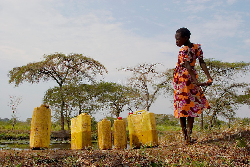 Empowering Victims of War- A young girl stretching with water jugs near the water whole. Canaan Family Farm lends land to displaced people from the Northern conflict to have them learn the benefits of work and empowerment. Rwakayata, Masindi, Uganda, Africa. December 2005 © Stephen Blake Farrington