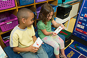 MR / Schenectady, NY. Zoller Elementary School (urban public school). Kindergarten classroom. Two bilingual students quiz each other with Spanish language vocabulary word cards. Left: boy, 6, African American /  Puerto-Rican American; Right: girl, 5; both are native Spanish speakers. MR: Car38, Cas12. ID: AM-gKw. © Ellen B. Senisi.
