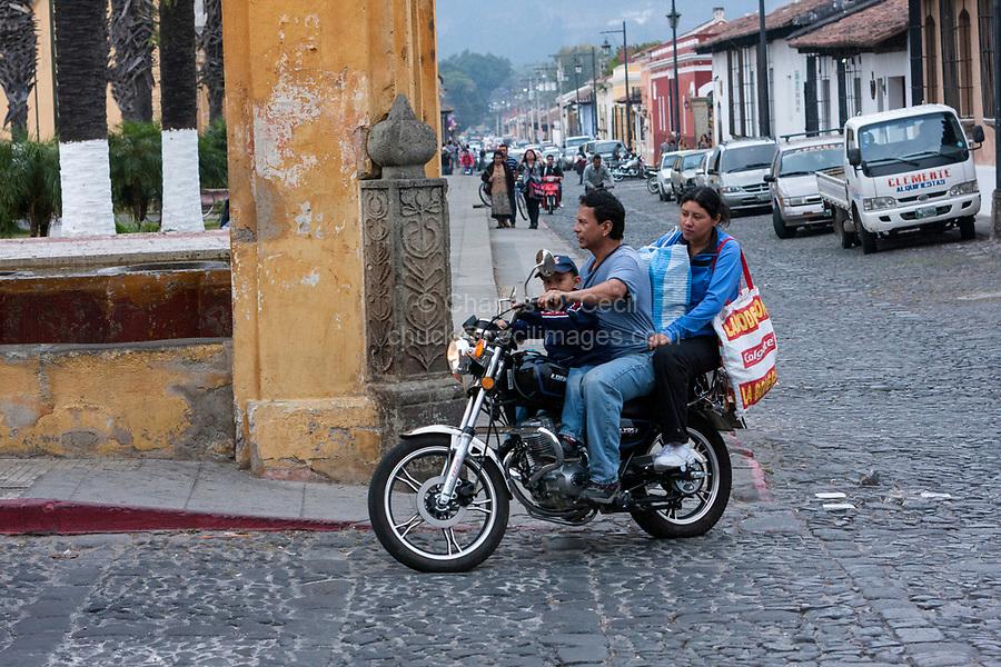 Antigua, Guatemala.  Couple on Motorbike with Young Boy, no Helmet.