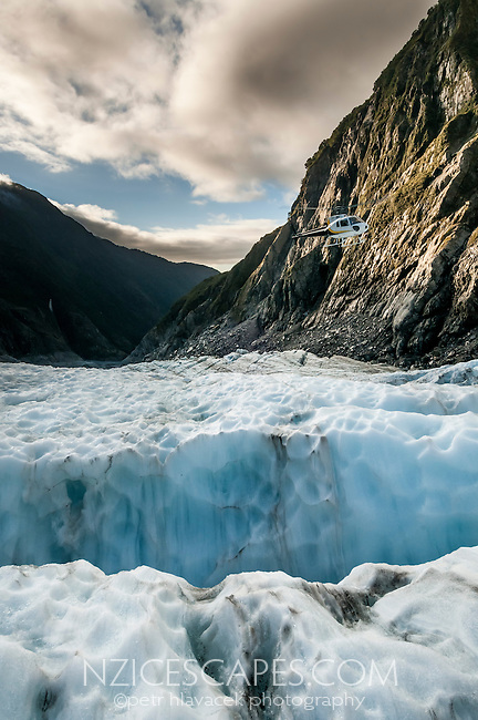 Looking across blue crevasses towards Waiho valley from Defiance Icefall of Franz Josef Glacier when sun sets. Helicopter in view, Westland National Park, West Coast, World Heritage, South Island, New Zealand