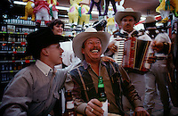 Father and son cross the Mexican border to celebrate a 21st birthday at a bar in a border town to Laredo, Texas.  The two laughed and sang with the Mariachi band in the atmosphere among other tourists among the pinatas.