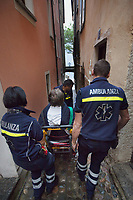 Switzerland. Canton Ticino. Morcote. A senior man is carried down a narrow alley with an emergency medical chair. He will go by ambulance to hospital for medical examination. The elderly man is suffering from deep vein thrombosis (DVT), which is a blood clot in the deep veins of the leg. Team paramedics wears a blue uniforms and works for theCroce Verde Lugano. Both men (R)(C) are professional certified nurses, the woman (L) is a volunteer specifically trained in emergency rescue. TheCroce Verde Lugano is a private organization which ensure health safety by addressing different emergencies services and rescue services. Volunteering is generally considered an altruistic activity where an individual provides services for no financial or social gain to benefit another person, group or organization. Volunteering is also renowned for skill development and is often intended to promote goodness or to improve human quality of life. 27.01.2018 © 2018 Didier Ruef