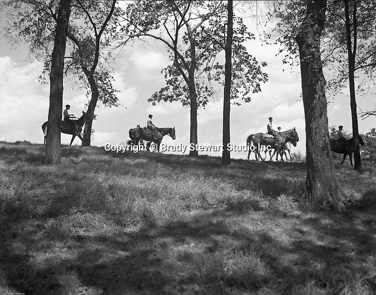Pittsburgh PA: View of boys riding Horses in Schenley Park.  Created in 1889 with land donated by heiress Mary Schenley, the park now contains 456 acres of trails, woods, and attractions.   The main attractions are Phipps Conservatory, Flagstaff Hill, Golf Course, Horse Stables, and swimming pool.