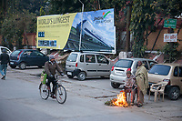India, Dehradun.  Two Men Warm themselves by a Fire on a Cold Winter Morning outside the Train Station.