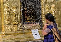 Nepal, Kathmandu, Swayambhunath.  Woman Praying in front of Buddhist Shrine.