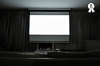 White projection screen in empty living room (Licence this image exclusively with Getty: http://www.gettyimages.com/detail/103810541 )
