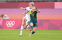KASHIMA, JAPAN - JULY 27: Ellie Carpenter #12 of Australia battles with Megan Rapinoe #15 of USA before a game between Australia and USWNT at Ibaraki Kashima Stadium on July 27, 2021 in Kashima, Japan.