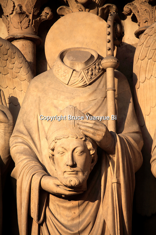 The statue of Saints Denis with his head on Portal of the Virgin. Notre Dame cathedral. city of Paris. Paris. France