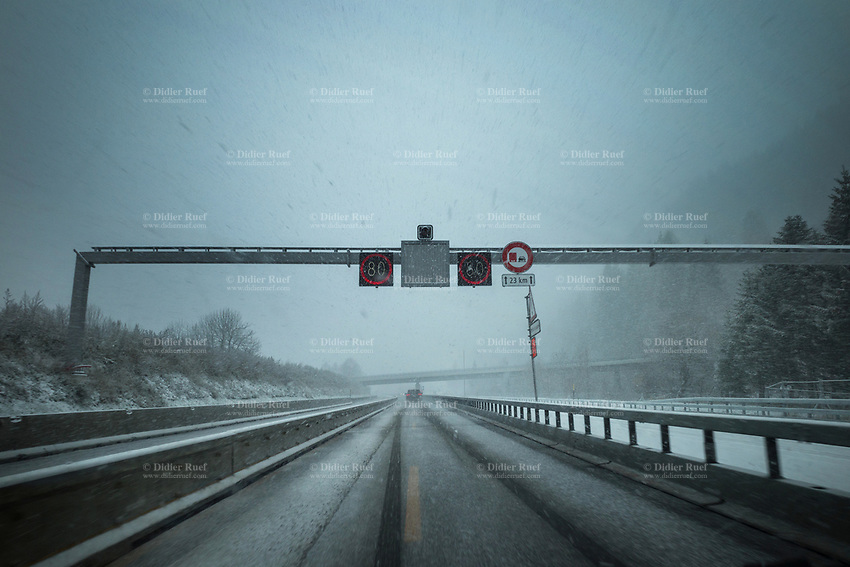 Switzerland. Canton Ticino. Airolo is a municipality in the district of Leventina. Cars on the motorway. Winter snow storm on A2 highway. Traffic signs and speed limit at 80 kilometers per hour.  1.12.2020 © 2020 Didier Ruef