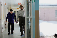 Caregiver Jean Claude Michel (right) walks with resident Michael Martin in the residences in Malone Park at the Fernald Developmental Center in Waltham, Massachusetts, USA.  Michael cannot speak.