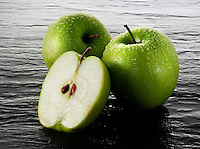 Whole and cut Granny Smiths apples stock photos