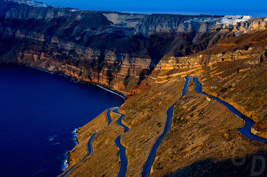 Looking like a liquid road the light in the late afternoon, the road leading to the Port area of Santorini Greece, this is where all the cruise ships usually anker, light on the Volcanic cliffs a geology wonder