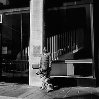 A security guard stands with an Alsatian dog outside the First National Bank (FNB) on Jorissen Street, Braamfontein.