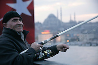 FISHING WITH THE SULEYMANIYE MOSQUE IN THE BACKGROUND, ISTANBUL, TURKEY