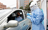 BOGOTA, COLOMBIA - MAY 13: A nurse takes a sample to a man in a COVID-19 drive-through test point on May 13, 2020 in Bogota. The drive-through test point, the first in Colombia, had a capacity to take 1,400 Covid-19 test a month with a cost of $50 dollars to every patient. (Photo by Leonardo Munoz/VIEWpress via Getty Images)