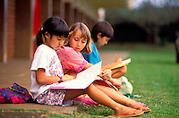 Photo of three local children reading and doing homework on the grassy area outside of their school.