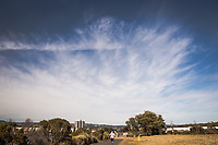 A jogger jogs away while another visitor, wearing a facemask, walks toward the camera under a blue sky filled with a spray of white clouds at the MLK Regional Shoreline during the COVID-19 pandemic.