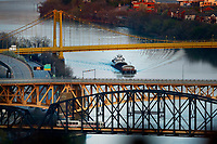 A barge passes an empty I-376, 10th Street, and Liberty Bridge as the Port Authority T goes across the bridge to Station Square as seen from the Mount Washington neighborhood on Tuesday April 7, 2020 in Pittsburgh, Pennsylvania. (Photo by Jared Wickerham/Pittsburgh City Paper)