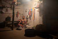 Every morning The pehlwan (an Indian wrestler) Jawla Trwatri takes a bath of smoke in his akhara ( a training hall for professional fighters ). Kolkata, India.
