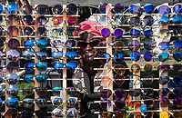 Black immigrant woman behind her wall of sunglasses for sale,<br /> Hempfest, Seattle, WA, USA.