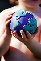 Boy (2-4) holding globe, close-up, mid section (focus on globe)