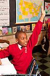 K-8 Parochial School Bronx New York Grade 5 male student  raising hand vertical
