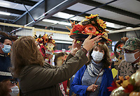 Margie Samuel of Bentonville (from left) lifts a decoration as Suzan Gualano of Naperville, Ill. and Bill Samuel look on, Thursday, October 15, 2020 at the Benton County Fairgrounds in Bentonville. The 4th annual Fall Y'all Craft Fair featured 40 vendors, half capacity to previous years, as well as local food trucks, photo opportunities and a pumpkin patch. The fair ends on Sunday. Check out nwaonline.com/2010013Daily/ for today's photo gallery. <br /> (NWA Democrat-Gazette/Charlie Kaijo)