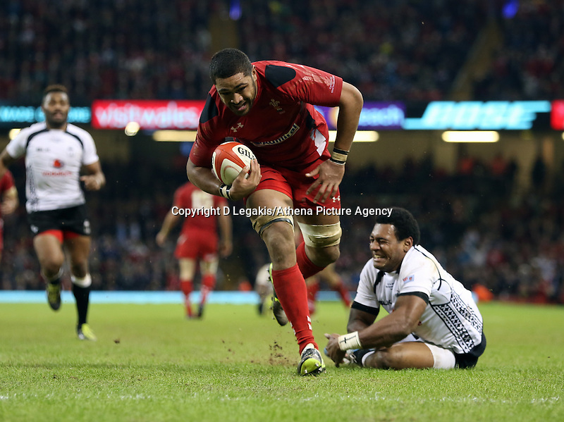 Pictured: Waisea Nayacalevu of Fiji (R) fails to stop Taulupe Faletau on his run for a try for Wales. Saturday 15 November 2014<br /> Re: Dove Men Series rugby, Wales v Fiji at the Millennium Stadium, Cardiff, south Wales, UK.
