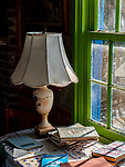 An antique lamp sits on a small table, with a collection of old books, next to a window.